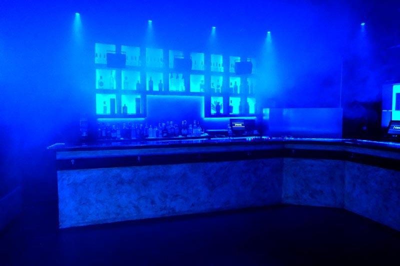 barra de fondo con botellas y luces azules y humo